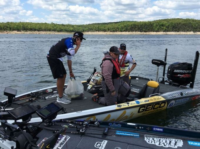 Carl Jocumsen transfers his fish to Mike McClelland's boat while conferring with tournament officials. (James Overstreet photo)